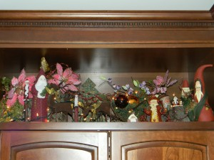 Christmas decorations, assorted santas above TV armoire